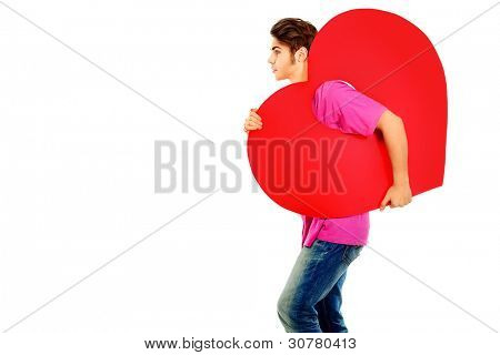 Happy young man walking with big red heart. Isolated over white background.