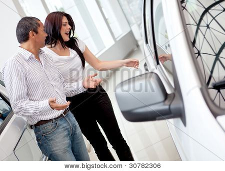 Loving couple at the dealership buying a car