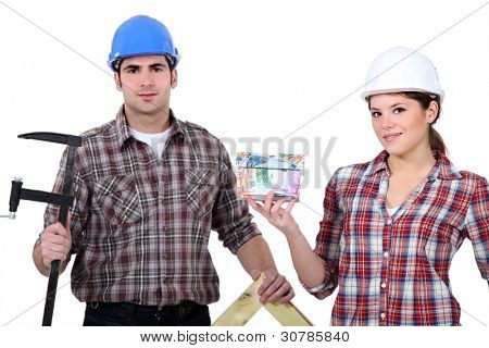 A team of tradespeople holding their tools and a house model