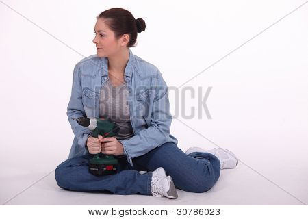Woman sat on floor with power drill