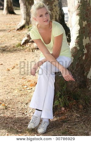Summery woman sitting by a tree