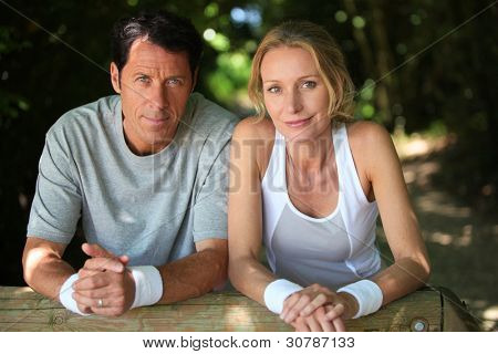 Sporty couple having a rest from exercise in the country