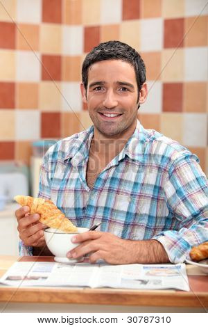 Man dunking a croissant into a cafe au lait at breakfast time