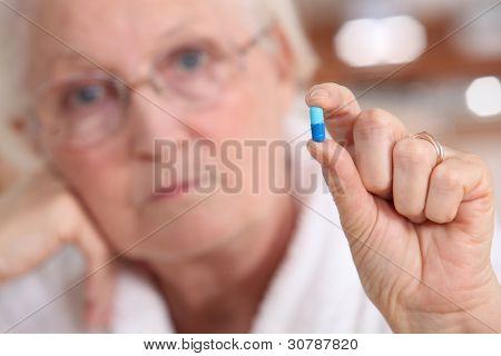 Elderly woman holding a capsule between her fingers