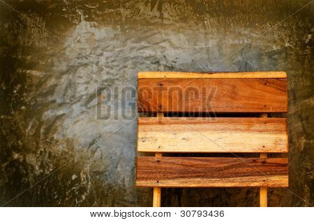 wooden chiar and concret wall.