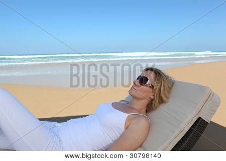 Woman lying on a lounge chair at the beach