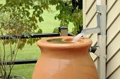 picture of downspouts  - Rain Barrel being filled during rain storm - JPG