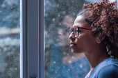 Lonely Black Woman Near Window Thinking About Something And Winter Snow poster