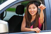 Beautiful Chinese Asian young woman or girl leaning out of a car in summer sunshine smiling with per poster