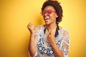 Young african american woman with afro hair wearing bikini and heart shaped sunglasses very happy an poster