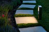 Square Tile Marble Path Illuminated By A Lantern In The Backyard, A Winding Path In The Flowerbed Ga poster