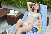 Beautiful Sexy Smiling Girl With Long Hair In A Bikini Lying On A Lounger Covered With Blue Pareo .  poster