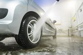 Man Cleaning Vehicle With High Pressure Water Spray Or Jet. Car Wash Details. Wash The Wheels With W poster