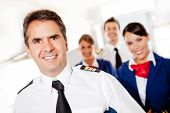 stock photo of cabin crew  - Captain with cabin crew in an airplane smiling - JPG