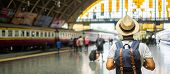 Young Man Traveler With Backpack Waiting For Train, Asian Backpacker With Hat Standing On Railway Pl poster