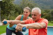 Side view of Caucasian female trainer assisting active senior Caucasian man to exercise with dumbbel poster