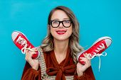 Young Girl With Red Gumshoes On Blue Background poster
