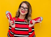 Young Woman In Red Striped Sweater With Gumshoes On Yellow Background poster