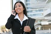stock photo of asian woman  - A pretty asian business woman on the cell phone outside office building - JPG