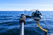 Fishing Rod Spinning With The Line Close-up. Fishing Rod In Rod Holder In Fishing Boat Due The Fishe poster