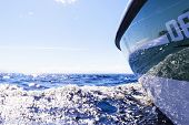 Side View Speeding Fishing Motor Boat With Drops Of Water. Blue Ocean Sea Water Wave Reflections Wit poster