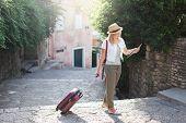 Girl Traveler Looks At City Map With Suitcase At Town Street In Europe. Woman Tourist Is Searching A poster