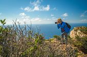 Female Tourist Standing On The Edge Of A Cliff And Photographing The Stunning Cliffs In Shipwreck Co poster