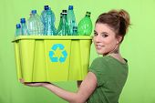 picture of segregation  - Woman recycling crate of plastic bottles - JPG