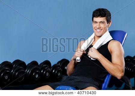 Athletic man rests sitting on blue simulator in gym