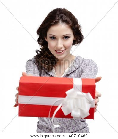 Young woman reaches out a gift wrapped in red paper, isolated on white