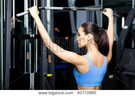 Athletic young woman works out on simulator in training gym