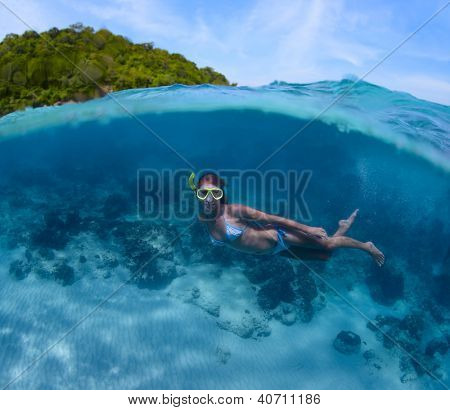 Underwater shoot of a young lady doing skin diving in tropical sea with green island on the background