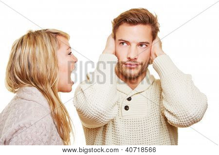 Young angry woman screaming and sulking man closing his ears