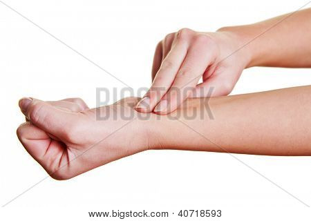 Two fingers measuring the blood pressure with feeling the pulse at the wrist