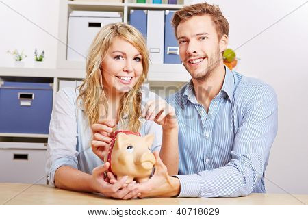 Young happy couple saving Euro money with a piggy bank