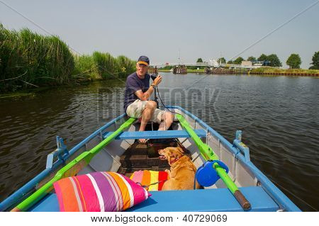 Senior man with dog in little rowingboat at Dutch river