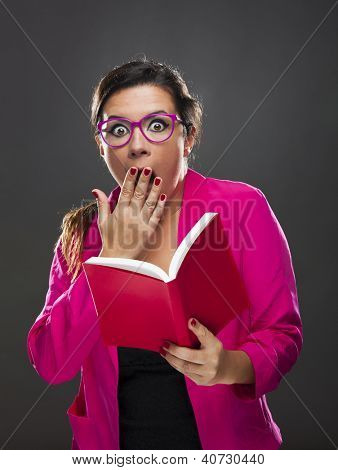 Middle aged woman with a astonished expression and holding a red book