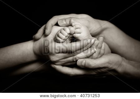 Parents Holding Their Child's Feet Gently