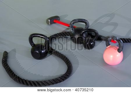 Kettlebells ropes and hammer in fitness gym floor