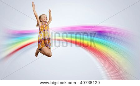Photo of little girl jumping and raising hands against rainbow background
