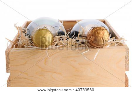 End view of two champagne bottles in a wood crate with packing material. Horizontal format closeup isolated on white.