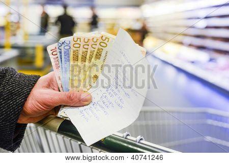 Mano, sosteniendo varios billetes de euro y una lista de compras con productos alimenticios, en un carrito de compras dentro de una sup