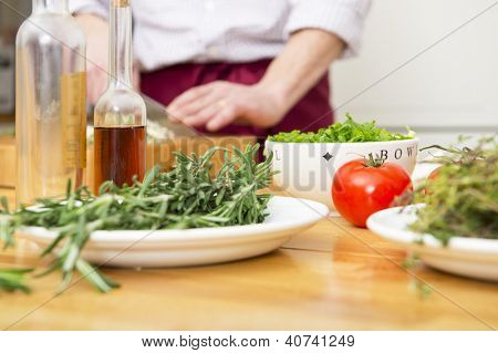 Tomato, thyme, rosemary, onions and bottles of vinaigrette on the workbench of a home chef, working with a cutting knife in the background