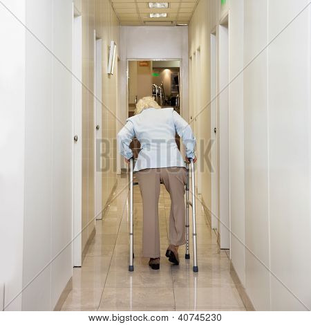 Rear view of woman with Zimmer frame walking in hospital corridor