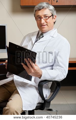 Portrait of mature male doctor holding clipboard while sitting on chair in clinic