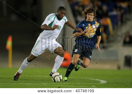 BARCELONA - JAN, 2: Nigerian player Bright Dike fights with Carles Puyol of Catalonia during the friendly match between Catalonia and Nigeria at Estadi Cornella on January 2, 2013 in Barcelona, Spain
