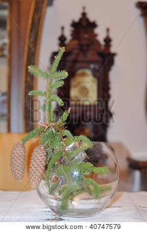 Christmas Tree Branch With Cones On The Background Of Clock