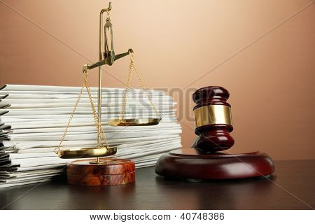 Golden scales of justice, gavel and folders on brown background