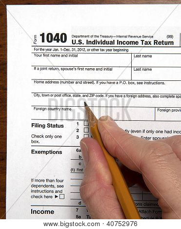 View of United States tax form with hand holding sharpened pencil