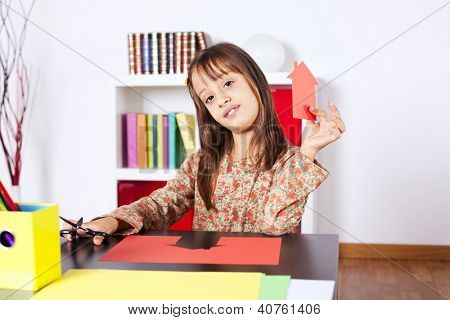 Litle girl cutting a house on a red paper